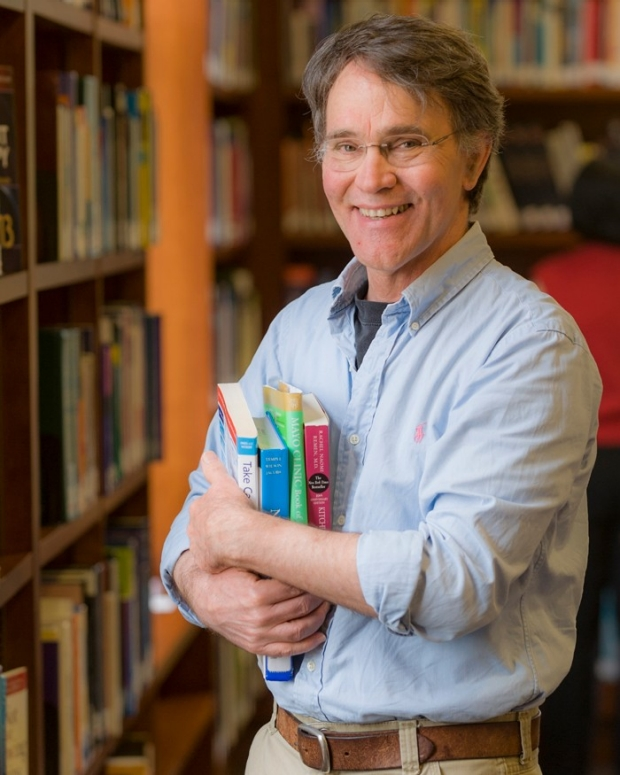 Man in library smiling and holding books