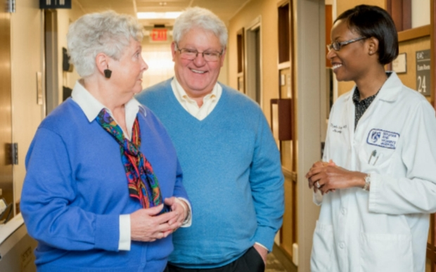 Female doctor speaking with older couple